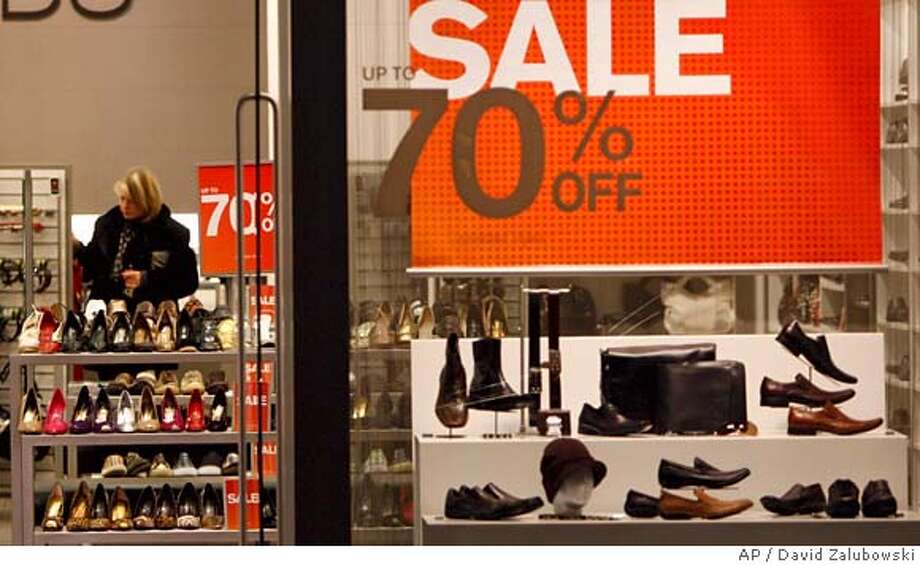 A sale sign hangs in the window of a shoe store in the west Denver suburb of Lakewood, Colo., as a shopper scans the sales rack in the background on Friday, Feb. 1, 2008. Shoppers put aside worries about the slumping economy to go to malls and auto dealerships in January. That propelled retail sales to a surprising rebound following a dismal December. (AP Photo/David Zalubowski) A FEB. 1, 2008 PHOTO. Photo: David Zalubowski