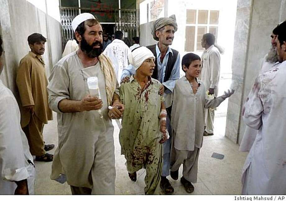 A child, who was injured in a bomb explosion in a market, is helped by his relatives after receiving initial treatment at a local hospital in Dera Ismail Khan, Pakistan on Sunday, June 14, 2009. A government official said the blast appeared to have been caused by a planted explosive device. (AP Photo/Ishtiaq Mahsud) Photo: Ishtiaq Mahsud, AP