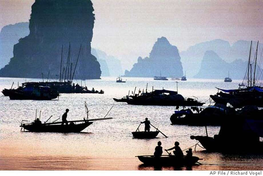 ** FOR IMMEDIATE RELEASE ** ** FILE ** Vietnamese fishermen start their morning fishing in Ha Long bay in northern Quang Ninh province in this Sept. 15, 2000 file photo. Starting in Jan. 2009, a global poll will allow people worldwide to vote and select the seven natural wonders of the world. (AP Photo/Richard Vogel, File) A SEPT. 15, 2000 FILE PHOTO. BEST QUALITY AVAILABLE. Photo: RICHARD VOGEL
