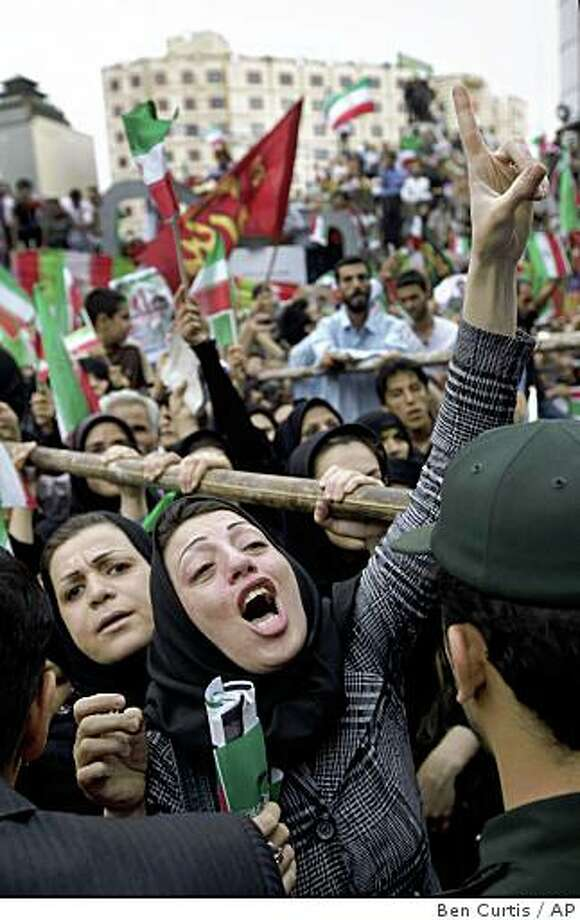"""An emotional supporter shouts out as tens of thousands of supporters of Iranian President Mahmoud Ahmadinejad gather in Vali Asr square for a rally attended by the president, in Tehran, Iran Sunday, June 14, 2009. Protesters set fires and smashed store windows Sunday in a second day of violence as groups challenging President Mahmoud Ahmadinejad's re-election tried to keep pressure on authorities but Ahmadinejad dismissed the unrest, the worst in a decade in Tehran, as """"not important."""" (AP Photo/Ben Curtis) Photo: Ben Curtis, AP"""