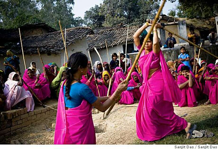 The 47-year-old leader of the Pink Gang, Sampat Pal Devi is seen teaching lathi (traditional bamboo baton used by police to control crowds) fighting skills to Aarti, one of the young members of the pink gang. A fiesty woman, barely educated, impoverished mother of five, Sampat Pal Devi has emerged as a messianic figure in the region.  Banda is one of the poorest parts of India's northern and most populous state, Uttar Pradesh. A gang of vigilantes, called the Gulabi Gang (pink gang)  its several thousand strong women members wear only pink saris is taking up lathi (against domestic violence and corruption. Photo: Sanjit Das