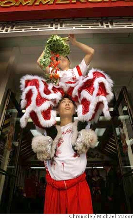 chinesenewyear_103_mac.jpg Lion Dancers, Peter Luong, (bottom) gives his brother Danny, a lift as he attaches an offering of food and notes for the Lion just before a performance along Washington St at Grant in Chinatown. The first day of the Lunar New Year gets underway today. Photographed in, San Francisco, Ca, on 2/7/08. Photo by: Michael Macor/ San Francisco Chronicle Mandatory credit for Photographer and San Francisco Chronicle No sales/ Magazines Out Photo: Michael Macor