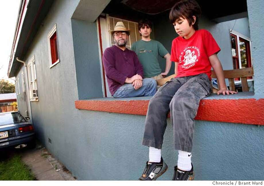 Alexander Barks, 10, right, is sad the family can't build a studio in the backyard. He plays the guitar. He is joined on his porch by father Don and brother Kenton. The Barks family tore down a garage in their backyard in Oakland planning to build a family music studio, but the value of the house was so low that they must put their plans on hold now. (Photo by Brant Ward/San Francisco Chronicle) Photo: Brant Ward