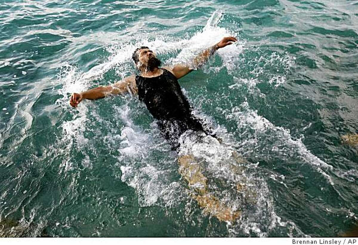 Former Guantanamo detainee Salahidin Abdulahat takes a swim in the Atlantic ocean off the shore near Hamilton, Bermuda, Sunday, June 14, 2009. Abdulahat is among four Chinese ethnic Uighurs who have just been released from U.S. military custody after years in Guantanamo, and are being resettled in Bermuda. (AP Photo/Brennan Linsley)