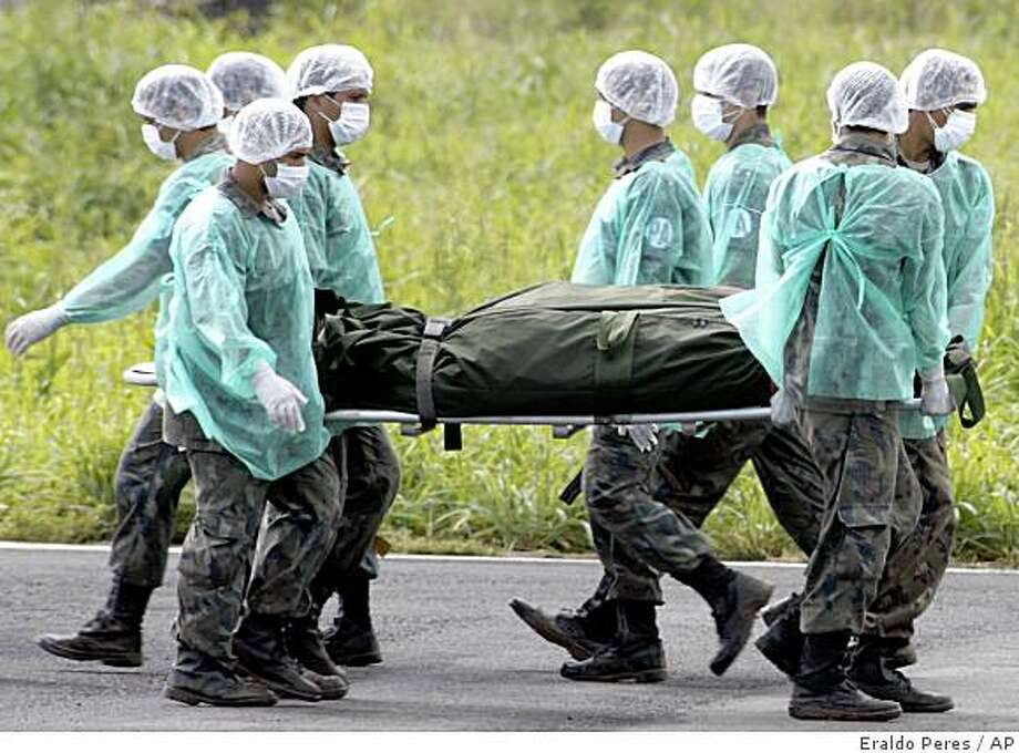 Brazilian Air Force personnel carry a body recovered during search operations of the missing Air France flight 447 in Fernando de Noronha island, off the northeast coast of Brazil, Thursday, June 11, 2009. As storms bore down on the crash zone off Brazil, a French submarine searched the depths of the Atlantic Ocean for the black boxes that hold the best hope of finding out what did happen to the plane when it flew into heavy storms May 31 with 228 people aboard. Photo: Eraldo Peres, AP