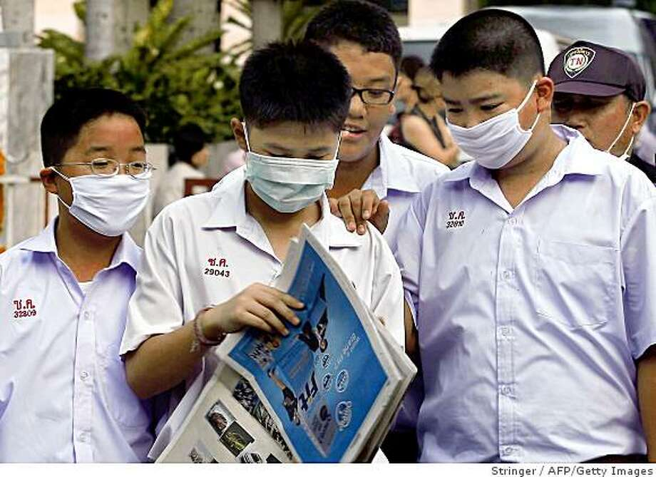 Thai students wear face masks at a school in Bangkok on June 11, 2009. Thailand announced 30 new confirmed cases of swine flu in the kingdom taking the total to 46 and said it expected that figure to continue to rise. The World Health Organization (WHO) will consult on June 11 with its emergency committee of flu experts, a body of scientists that could recommend the declaration of a swine flu pandemic, a WHO spokesman said. On June 10 the number of A(H1N1) infections reported to the WHO by 74 countries reached 27,737, including 141 deaths. AFP PHOTO (Photo credit should read STR/AFP/Getty Images) Photo: Stringer, AFP/Getty Images
