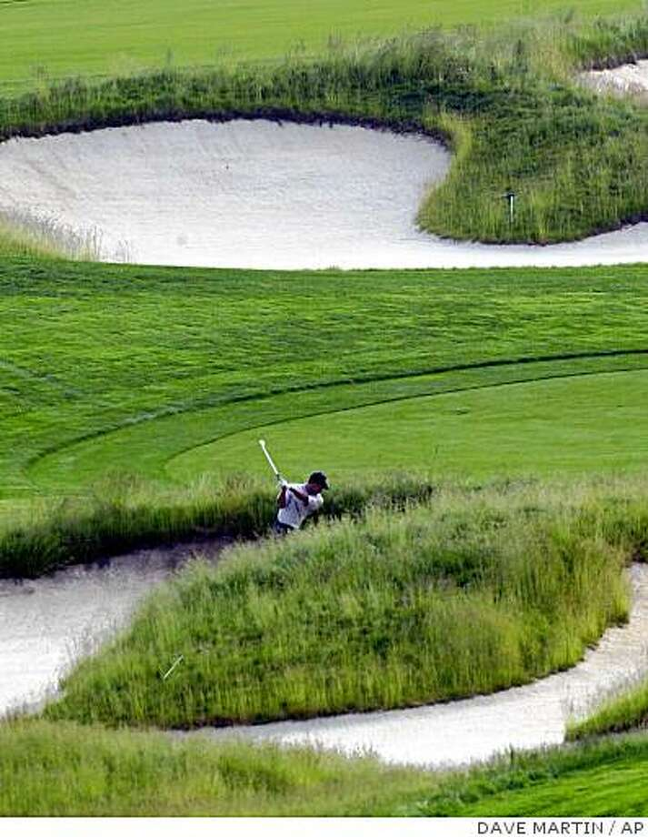 Tiger Woods hits from the bunker on the sixth hole Tuesday, June 11, 2002, at the U.S. Open Golf Championship at the Black Course of Bethpage State Park in Farmgindale, N.Y. (AP Photo/Dave Martin) Photo: DAVE MARTIN, AP