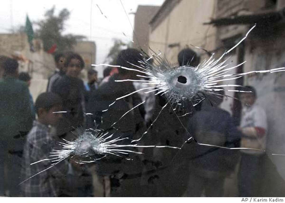 """People are seen through bullet riddled windscreen standing in front of a house in Sadr City after an overnight US troops raid Thursday, Feb. 7 2008. Seventeen people were arrested in the raid. The U.S. military said it was targeting """"criminal elements"""". Two people were wounded, and one of those subsequently died. (AP Photo/Karim Kadim)"""