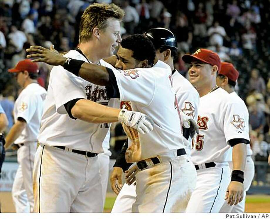 Houston Astros' Geoff Blum, left, is hugged by teammate Miguel Tejada after Blum hit the game-winning RBI single to beat the Chicago Cubs 2-1 in 13 innings in a baseball game, Thursday, June 11, 2009, in Houston. (AP Photo/Pat Sullivan) Photo: Pat Sullivan, AP