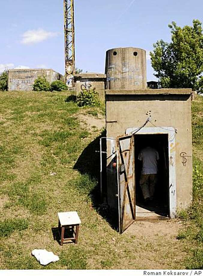 In this photo taken on May 26, 2009,  a man enters a bomb shelter on Export Street just north of downtown Riga, Latvia. This small facility, built a half-century ago to accommodate the port's managers, is usually ankle-deep in water. It is so damp that the guide refuses to switch on the light for fear it will spark an electrical shortage.  (AP Photo/Roman Koksarov) Photo: Roman Koksarov, AP