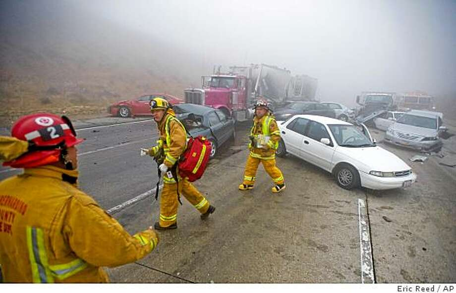 Authorities attend to the injured after a multi-vehicle collision in the heavy fog at the Cajon Pass on Interstate 15 near Oak Hills, Calif., Wednesday, June 10, 2009. As many as 50 vehicles were involved in a chain-reaction accident early Wednesday in fog on a mountain highway, with injuries reported and wreckage scattered for a half-mile, authorities said. (AP Photo/Eric Reed) Photo: Eric Reed, AP