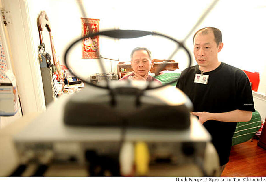 Tyler Tan, right, of Self-Help for the Elderly sets up a digital receiver for Ton Lenna in Oakland, Calif., on Friday, June 12, 2009. Photo: Noah Berger, Special To The Chronicle