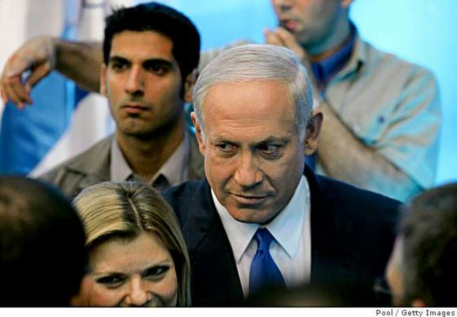 RAMAT GAN, ISRAEL - JUNE 14:  Israel's Prime Minister Benjamin Netanyahu (C) and his wife, Sarah, are surrounded by body guards after his speech at Bar-Ilan University on June 14, 2009 in Ramat Gan near Tel Aviv. Netanyahu accepted on Sunday the U.S.-backed goal of a Palestinian state but didn't meet President Barack Obama's demand to stop Jewish settlement expansion.   (Photo by Baz Ratner-Pool/Getty Images) Photo: Pool, Getty Images