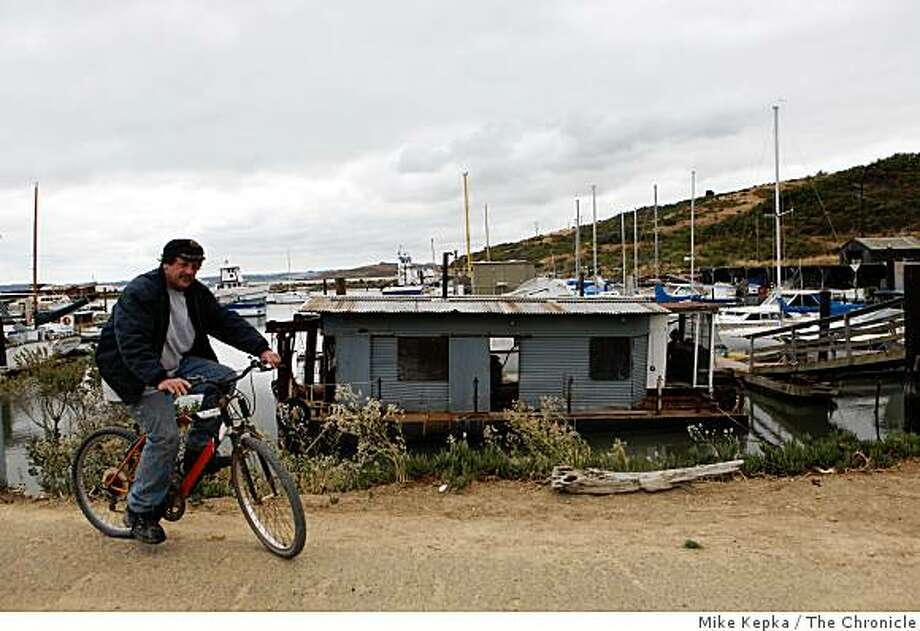 John Kingham, a twenty year resident at the Point San Pablo Yacht Harbor, rides his bike home on Monday June 8, 2008 in Richmond, Calif. They harbor is for sale and Kingham says he's not sure he'd be ready to join the regular world if he had to leave. Photo: Mike Kepka, The Chronicle