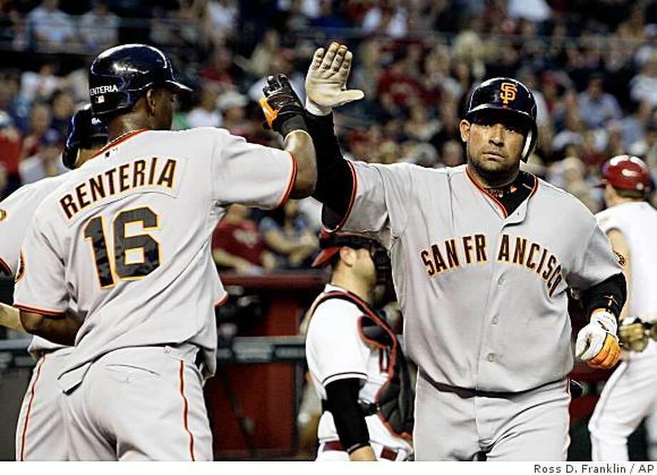 San Francisco Giants' Bengie Molina, right, gets a high-five from teammate Edgar Renteria (16) after Molina's home run against the Arizona Diamondbacks in the third inning of a baseball game Wednesday, June 10, 2009, in Phoenix. Photo: Ross D. Franklin, AP