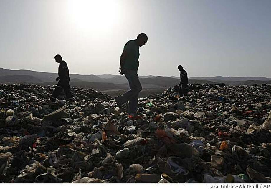 Garbage men search for a mattress that reportedly contains one million dollars in the landfill of Efeh, Wednesday, June 10, 2009. An Israeli woman mistakenly threw out a mattress she said had almost $1 million inside, setting off a frantic search through tons of garbage at a number of landfill sites on Wednesday. (AP Photo/Tara Todras-Whitehill) Photo: Tara Todras-Whitehill, AP