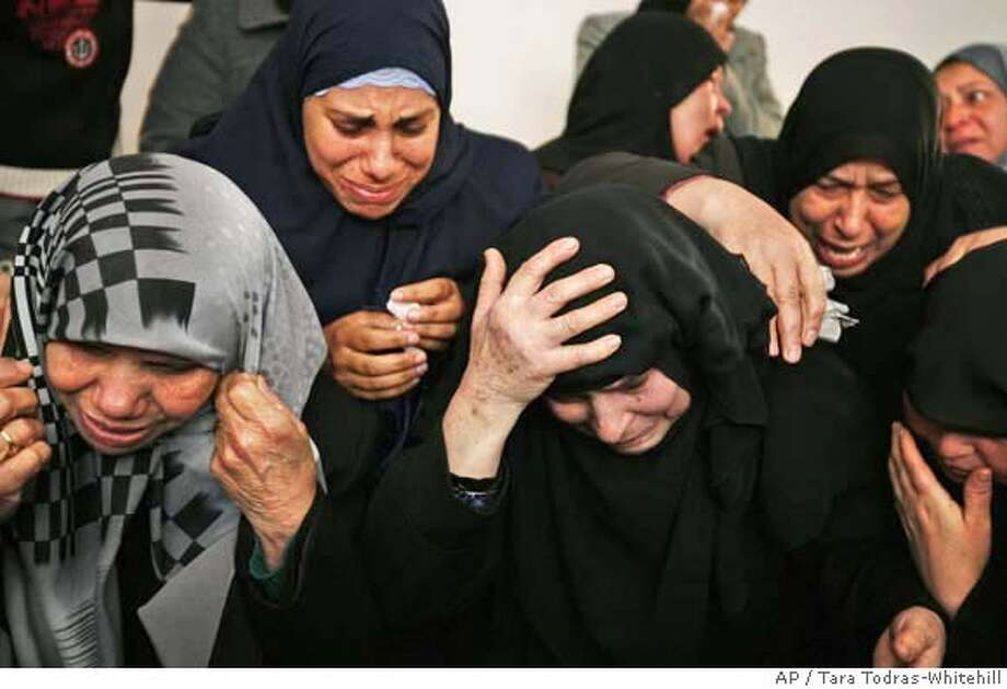 Palestinian relatives of Hamas militant, Hamouda Sharafa Tufha, center, killed during an Israeli army operation, mourn during his funeral in Gaza City Thursday Feb. 7, 2008. Israeli ground forces backed by warplanes exchanged fire with Hamas gunmen in the northern Gaza Strip on Thursday, killing a teacher and six militants in escalating violence that is hobbling peace efforts. (AP Photo/Tara Todras-Whitehill) Photo: TARA TODRAS-WHITEHILL