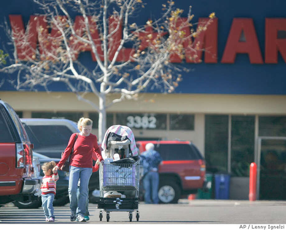 Ashley Tarbox pushes her shopping cart with her three children in tow at a Wal-Mart in San Diego, Thursday Feb. 7, 2008. The nation's retailers delivered more evidence of a stumbling economy Thursday, as merchants reported their weakest January performance in nearly four decades, extending a malaise that has deepened since the holiday shopping season. (AP Photo/Lenny Ignelzi) Photo: Lenny Ignelzi