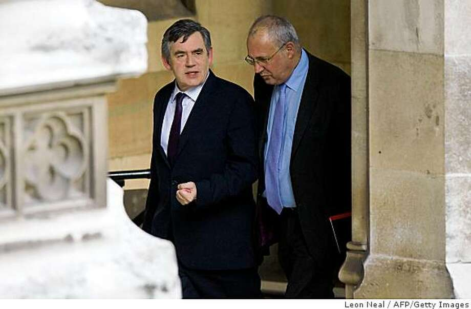 British Prime Minister Gordon Brown, flanked by an unidentified person, leaves the House of Commons in central London on June 8, 2009, following a meeting of the Parliamentary Labour Party. Brown's Labour was beaten into third place in the European elections, behind fringe anti-Europeans the UK Independence Party (UKIP), leaving him fighting for his job after 11 ministers resigned in recent days. AFP PHOTO/Leon Neal (Photo credit should read Leon Neal/AFP/Getty Images) Photo: Leon Neal, AFP/Getty Images