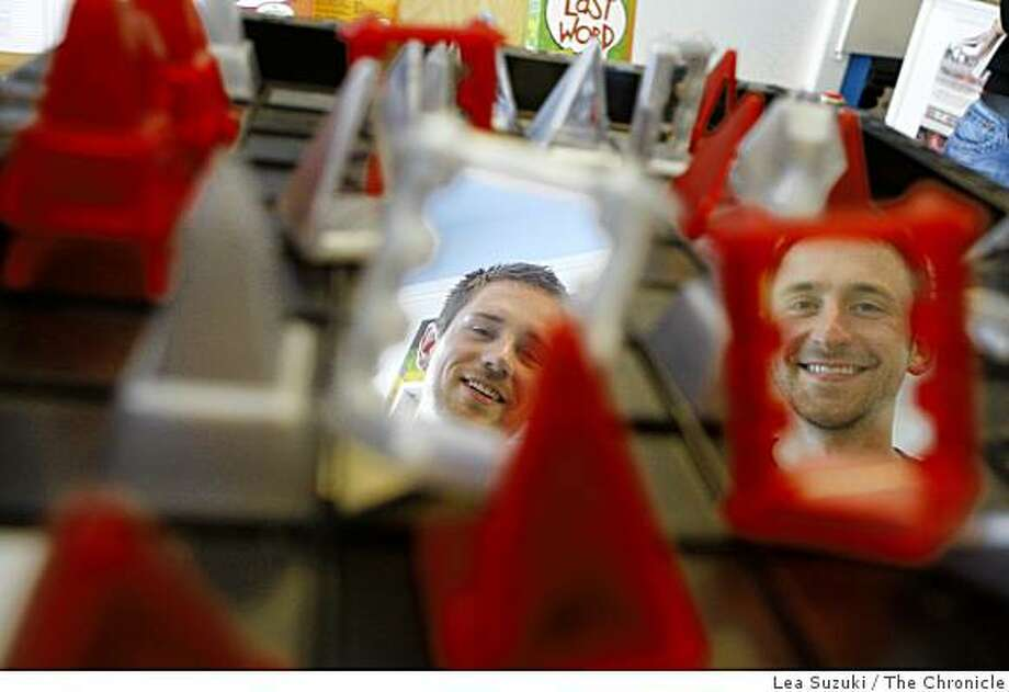 "Shane Alan (l to r) and Erik Mantsch, owners of ""Just Awesome"" photographed at their store reflected in game pieces from a game called ""Khet"" on display at their store in San Francisco,Calif. on Monday, June 7, 2009. Photo: Lea Suzuki, The Chronicle"