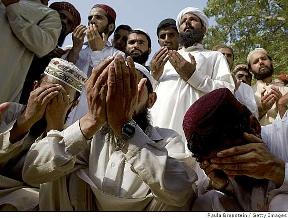 LAHORE, PAKISTAN - JUNE 13:  Pakistani men pray during a memorial service the morning after a suicide bomber killed moderate Cleric Sarfraz Naeemi at the Dar-ul Aloom Jamia Naeemia religious school June 13, 2009 in Lahore, Pakistan. Naeemi had openly supported the Pakistani government offensive against the Taliban, becoming a target for his moderate beliefs. Six others were killed in the attack in Lahore as well.  (Photo by Paula Bronstein/Getty Images) Photo: Paula Bronstein, Getty Images