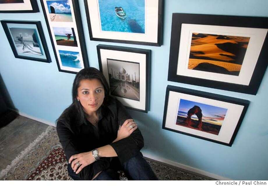 Simin Marefat sits with framed photographs she's taken during her travels at her home in San Francisco, Calif. on Friday, Jan. 11, 2008. Marefat, trained as a nurse, has travelled independently to over 60 countries and showed up at orphanages and clinics to volunteer her medical expertise. Photo: PAUL CHINN
