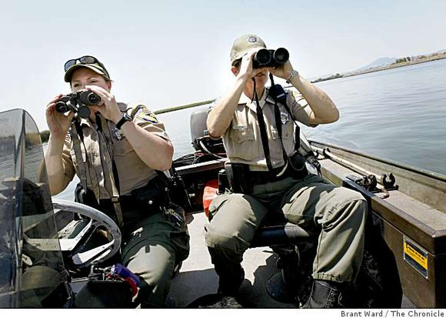 State Fish and Game officers Jessica Jacobsen (left) and Nicole Kozicki check on a boat in the Delta before approaching it. Game wardens across California are finding that hard economic times can be deadly for animals, poaching is on the rise. Photo: Brant Ward, The Chronicle
