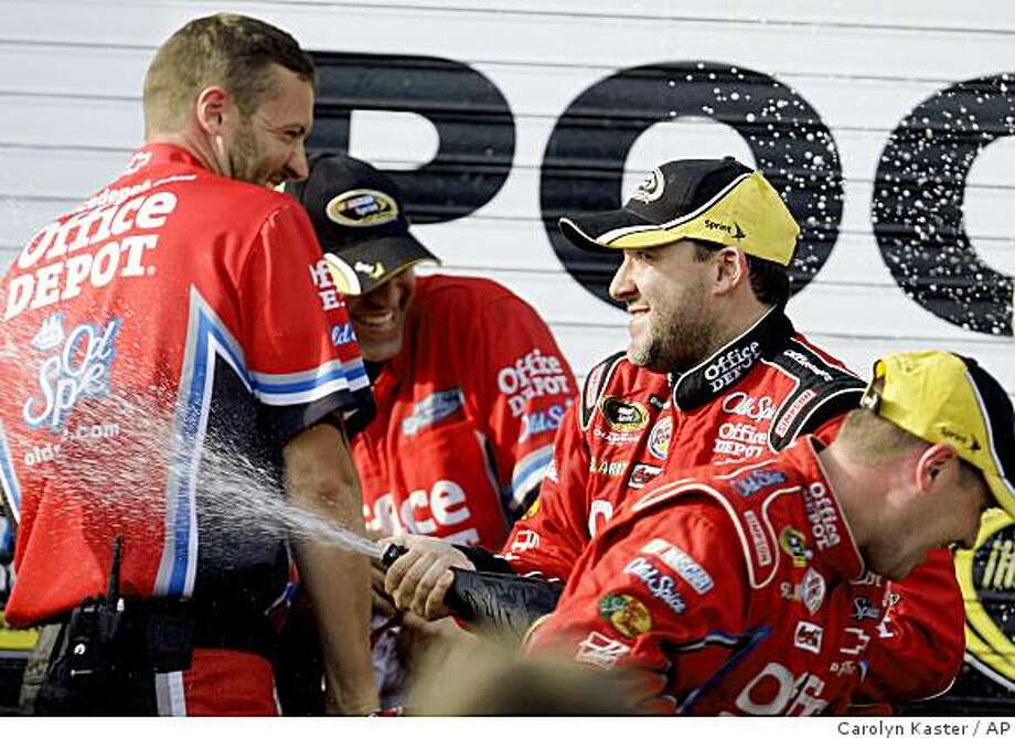 Tony Stewart celebrates with champagne in victory lane at Pocono Raceway in Long Pond, Pa., after winning the NASCAR Pocono 500 auto race Sunday, June 7, 2009. (AP Photo/Carolyn Kaster) Photo: Carolyn Kaster, AP