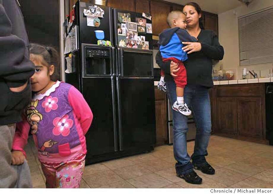 "rentforclose01_012_mac.jpg 4 year old Dalilah, snuggles up to her dad Jesse as Adriana holds her son Jesus, 19 months, she is expecting her third child in March. Adriana Diharce found a notice on her front doorstep advising her of an ""Trustee Sale"", so she opened it and found out that the home she and her husband are renting was being sold in a foreclosure auction. Photographed in, Hayward, Ca, on 1/30/08. Photo by: Michael Macor/ San Francisco Chronicle Mandatory credit for Photographer and San Francisco Chronicle No sales/ Magazines Out Photo: Michael Macor"