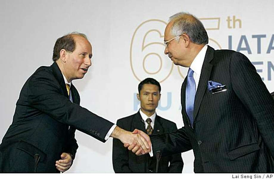 Senior Vice President of International Air Transport Association (IATA) Thomas Windmuller, left, shakes hand with Malaysian Prime Minister Najib Razak at the 65th IATA Annual General Meeting in Kuala Lumpur, Malaysia, Monday, June 8, 2009. The world's airlines are collectively expected to lose $9 billion in 2009 with revenues to shrink by $80 billion from a year ago, as the economic crisis saps air travel and cargo demand, a key industry body warned Monday. (AP Photo/Lai Seng Sin) Photo: Lai Seng Sin, AP