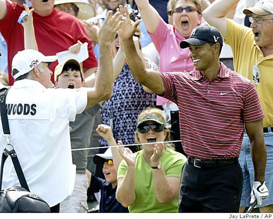 Tiger Woods, right, celebrates with his caddie Steve Williams after chipping in for eagle on the 11th hole during the final round of the Memorial golf tournament Sunday, June 7, 2009, in Dublin, Ohio. (AP Photo/Jay LaPrete) Photo: Jay LaPrete, AP
