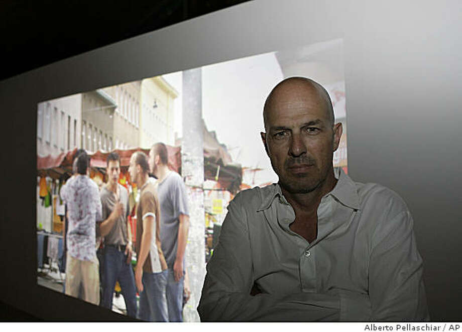"""Canadian artist Mark Lewis poses inside the Canadian pavilion as one of the four films he is presenting with the name """"Cold Morning"""" runs behind, on the second day of vernissage of the 53rd Biennale International Art Exhibition in Venice, Italy, Friday, June 5, 2009. Photo: Alberto Pellaschiar, AP"""