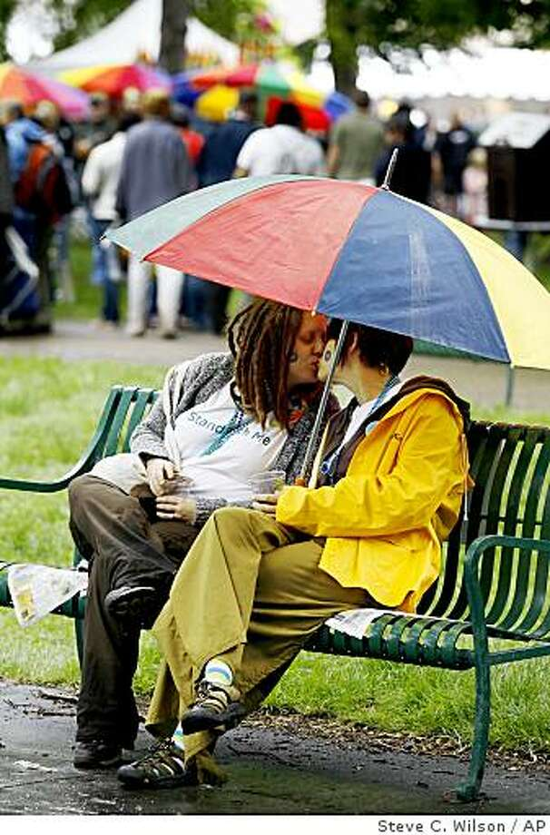 Recently married couple Katie Jacobsen-O'Farrell, left and her partner Jeana, right, share an umbrella at the Utah Pride Festival Sunday, June 7, 2009 in Salt Lake City. Cleve Jones, an activist who worked alongside slain gay rights leader Harvey Milk is calling for an October march on Washington to demand that Congress establish equal rights for the lesbian, gay and transgender community. Jones said Sunday in Salt Lake City that the march will launch a nationwide grass roots campaign. (AP Photo/Steve C. Wilson) Photo: Steve C. Wilson, AP