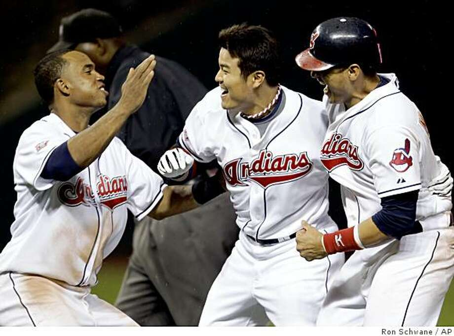 Cleveland Indians Shin-Soo Choo, center, celebrates with Victor Martinez, right, and Luis Valbuena after hitting a game-winning single off Kansas City Royals Kyle Farnsworth in the tenth inning during a baseball game Thursday June 11, 2009, in Cleveland. The Indians won 4-3 in ten innings. (AP Photo/Ron Schwane) Photo: Ron Schwane, AP