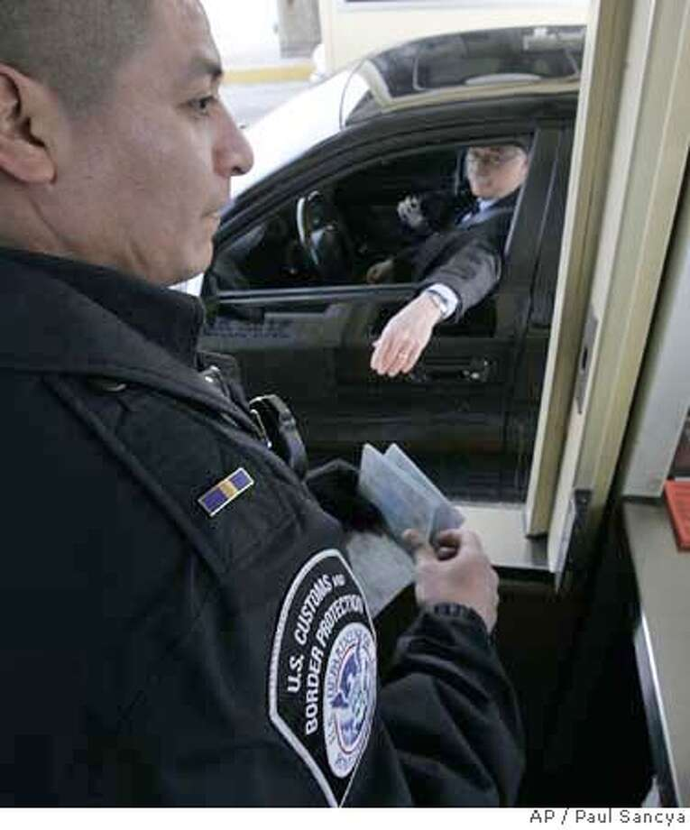 U.S. Customs officer Eliseo Sanchez checks a drivers documentation arriving from Canada at the Ambassador Bridge in Detroit, Wednesday, Jan. 30, 2008. U.S. officials begin what amounts to a test run of new identification requirements for people entering the country from Canada and Mexico Thursday. Americans and Canadians who enter will no longer be able to simply declare their nationality and enter the U.S. They will be required to show some document to prove citizenship beyond a driver's license, though travelers won't be turned away without the extra ID. Mexican citizens already are required to show proof of citizenship at the border. (AP Photo/Paul Sancya) Photo: Paul Sancya