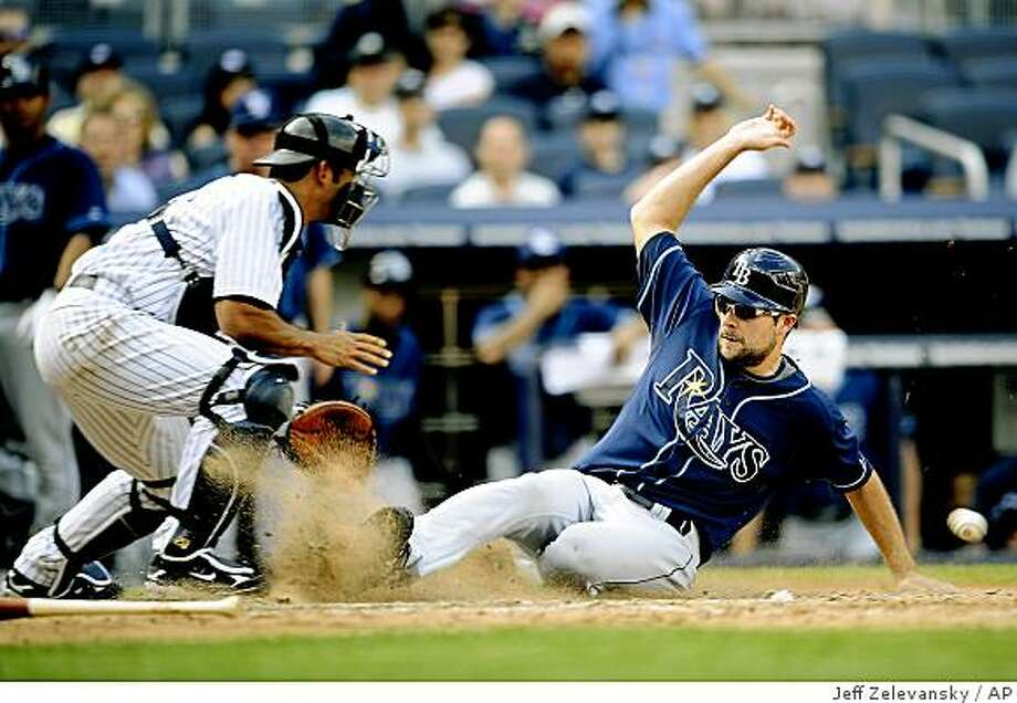 Tampa Bay Rays pinch runner Andy Sonnanstine scores ahead of a throw to New York Yankees catcher Jorge Posada in the ninth inning of a baseball game at Yankee Stadium, Saturday, June 6, 2009 in New York. (AP Photo/Jeff Zelevansky) Photo: Jeff Zelevansky, AP