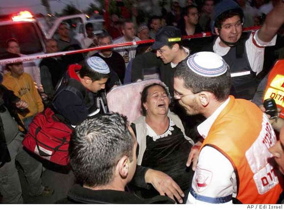 Israeli paramedics evacuate a wounded woman from her house moments after a rocket fired by Palestinians militants hit Sderot, southern Israel, Tuesday, Feb. 5, 2008. Israeli attacks on Tuesday killed eight Hamas militants in the Gaza Strip. Hamas retaliated with a rocket barrage on the southern Israeli town of Sderot. The rockets hit a house and seriously wounded one person, police and rescue workers said, and electricity was knocked out in part of the town, plunging it into darkness. (AP Photo/Edi Israel) ** ISRAEL OUT ** ISRAEL OUT Photo: Edi Israel