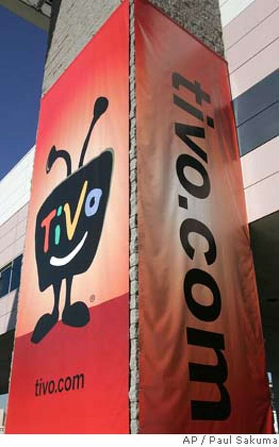 A large TiVo sign hangs outside the Consumer Electronics Show in Las Vegas, Wednesday, Jan. 9, 2008. A federal appeals court on Thursday upheld TiVo Inc.'s claims that Dish Network Corp. infringed on one of its patents, sending TiVo's shares up almost 29 percent. The Court of Appeals for the Federal Circuit agreed with a lower court that digital video recorders distributed by Dish, formerly known as EchoStar Communications Corp., violated the software elements of TiVo's patent. (AP Photo/Paul Sakuma) Photo: Paul Sakuma