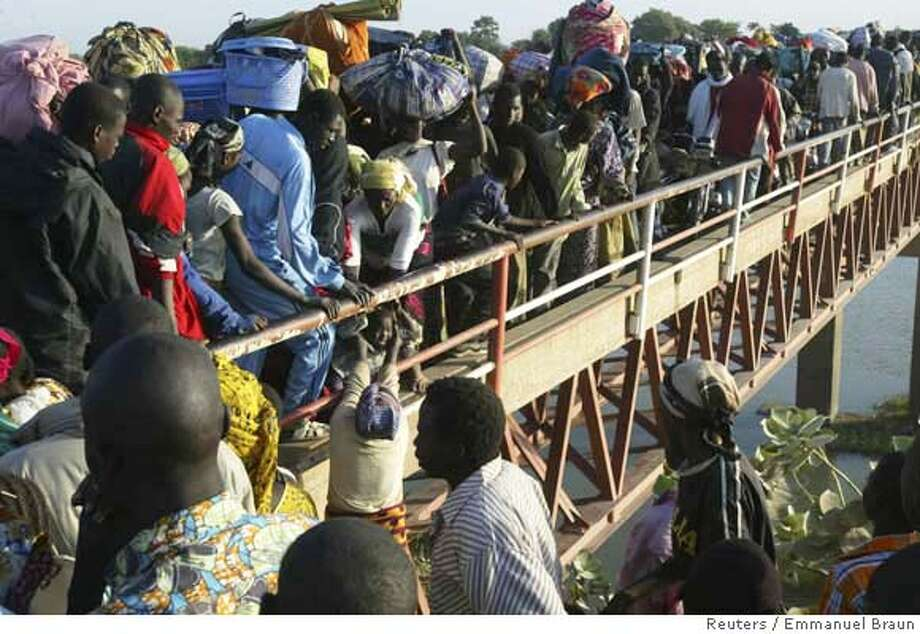 People carry their belongings as they pour across the Ngueli bridge over the Logone-Chari river into Cameroon fleeing fighting in N'Djamena February 4, 2008. The U.N. Security Council urged countries on Monday to support Chad's government against rebels, opening the way for foreign aid to help thousands who have fled a two-day assault on the capital. REUTERS/Emmanuel Braun (CHAD) 0 Photo: STAFF