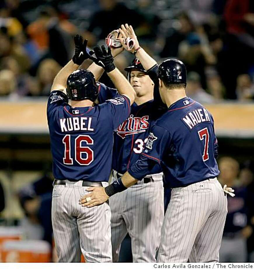 Joe Mauer, right and Justin Morneau, center, congratulate Jason Kubel after scoring on his three-run Home Run in the top of the seventh inning. The Oakland Athletics played the Minnesota Twins at the Oakland-Alameda County Coliseum in Oakland, Calif., on Tuesday, June 9, 2009. Photo: Carlos Avila Gonzalez, The Chronicle