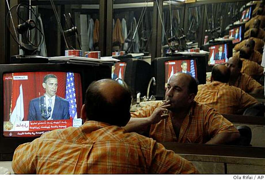 A Syrian barber, reflected in a mirror, listens to the speech of U.S. President Barack Obama on a TV screen in his shop in Damascus, Syria, Thursday, June 4, 2009. Muslims greeted President's Barack Obama's speech from Cairo Thursday as a mark of a changed American attitude toward them and a new policy on the Middle East, but some insisted they still need to see action to back up his words. (AP Photo/Ola Rifai) Photo: Ola Rifai, AP