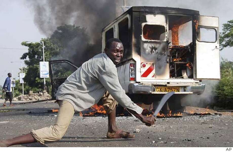 An opposition supporter scrapes a machete along the road next to a burning vehicle set on fire in Kisumu, Kenya, Thursday, Jan. 31, 2008, following the shooting of Kenyan opposition lawmaker David Too by a police officer in Eldoret. Within minutes of the news reaching the opposition stronghold of Kisumu gangs of men armed themselves with machetes, set up burning barricades, businesses shut down and workers began to flee from the town center. (AP Photo) Photo: Associated Press