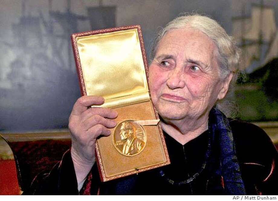 Doris Lessing holds up the 2007 Nobel Prize for Literature medal after being presented it by the Ambassador of Sweden Staffan Carlsson, during a ceremony at the Wallace Collection art gallery in London, Wednesday Jan. 30, 2008. The 88-year-old writer suffers back problems and was not well enough to travel to Stockholm for the official Nobel prize-giving ceremony on Dec. 10. (AP Photo/Matt Dunham) Photo: MATT DUNHAM