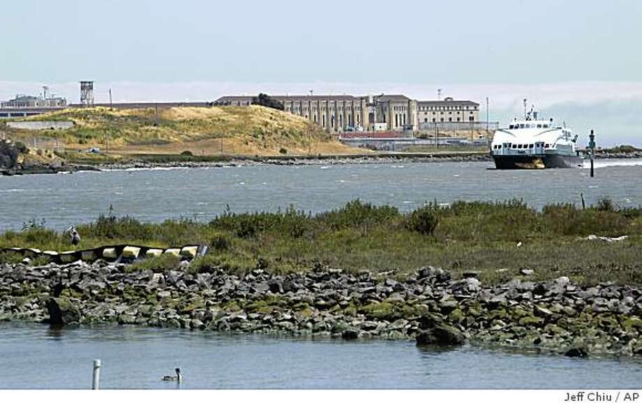 This photo from Thursday, May 28, 2009 shows San Quentin prison, background, as the Larkspur Ferry arrives in Larkspur, Calif. Gov. Arnold Schwarzenegger's plan to put some of his state's biggest landmarks up for sale to help erase a $24 billion budget deficit is fraught with questions, chief among them: How can California taxpayers possibly get a good deal in this slumping real estate market? (AP Photo/Jeff Chiu) Photo: Jeff Chiu, AP