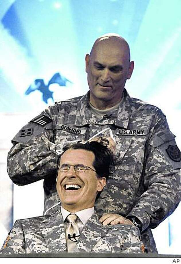 In this handout photo taken Sunday, June 7, 2009, released by the U.S. military, comedian Stephen Colbert, from the Comedy Central television program gets a military style haircut from General Raymond Odierno, Commander of the Multinational Corps, Iraq, during the taping the first of four shows at Camp Victory in Baghdad, Iraq, Sunday, June 7, 2009. Photo: AP