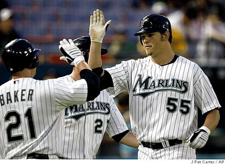Florida Marlins pitcher Josh Johnson (55) celebrates his three-run home run with teammate John Baker (21) and Jeremy Hermida, center, during baseball game action in the fifth inning Thursday, June 4, 2009, in Miami against the Milwaukee Brewers. (AP Photo/J Pat Carter) Photo: J Pat Carter, AP