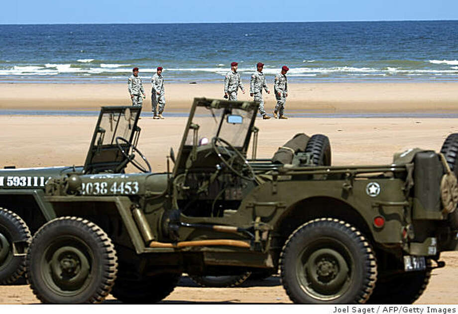 Jeeps from June 6, 1944 are displayed as US soldiers walk on Omaha Beach on June 4, 2009 in Colleville-sur-Mer, Normandy, western France, during preparations of the ceremonies commemorating the 65th anniversary of the D-Day Allied landings on the beaches of Normandy. US President Barack Obama will meet his French counterpart Nicolas Sarkozy and attend a ceremony at a cliff-top US war cemetery. British Prime Minister Gordon Brown, Prince Charles and Canadian Prime Minister Stephen Harper will also attend the solemn commemoration at Colleville-sur-Mer, which overlooks the US landing zone dubbed, Omaha Beach.   AFP PHOTO / JOEL SAGET (Photo credit should read JOEL SAGET/AFP/Getty Images) Photo: Joel Saget, AFP/Getty Images