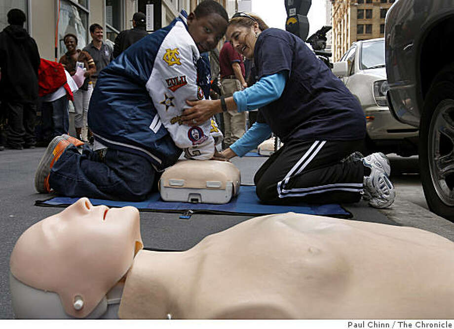 Ten-year-old Ivory Bivins gets a 90-second CPR lesson from Linda Clem when the San Francisco Paramedics Association offered free sidewalk  training sessions during the lunch hour in San Francisco, Calif., on Thursday, June 4, 2009. Photo: Paul Chinn, The Chronicle