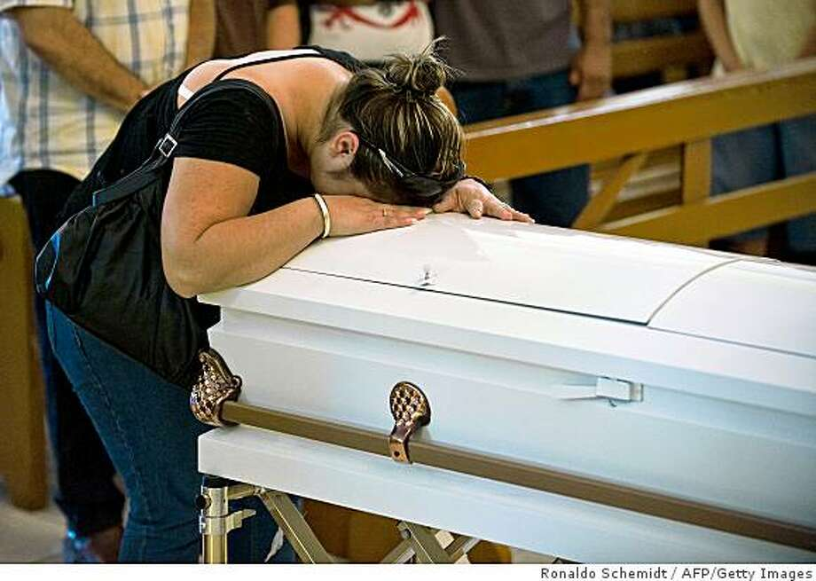 The unidentified mother of 2-year old Axel, who was one of the 38 children to lose their lives in a daycare center fire on June 5, cries over his coffin during the child's funeral in Hermosillo, Sonora state, Mexico on June 7, 2009. A blaze raced through the daycare center late on June 5 taking the lives 38 children between the ages of 3 months and 4 years, while 23 more are hospitalized, of which 15 are in critical condition. TOPSHOTS/AFP PHOTO/Ronaldo Schemidt (Photo credit should read Ronaldo Schemidt/AFP/Getty Images) Photo: Ronaldo Schemidt, AFP/Getty Images
