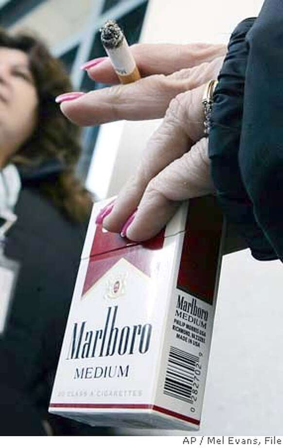 ** FILE ** A woman smokes a Marlboro Medium cigarette in Trenton, N.J. in this Jan. 31, 2007 file photo. Cigarette maker Altria Group Inc. on Wednesday, Jan. 30, 2008 said its fourth-quarter profit fell 26 percent due to a gain from a reorganization in 2006 that boosted the prior year's results. (AP Photo/Mel Evans, file) JAN 31, 2007 FILE PHOTO Photo: Mel Evans